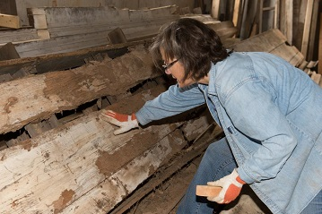My wife, Sharon cleaning dirt off Tara's ceiling to reveal the size of the brick columns that were holding it up.